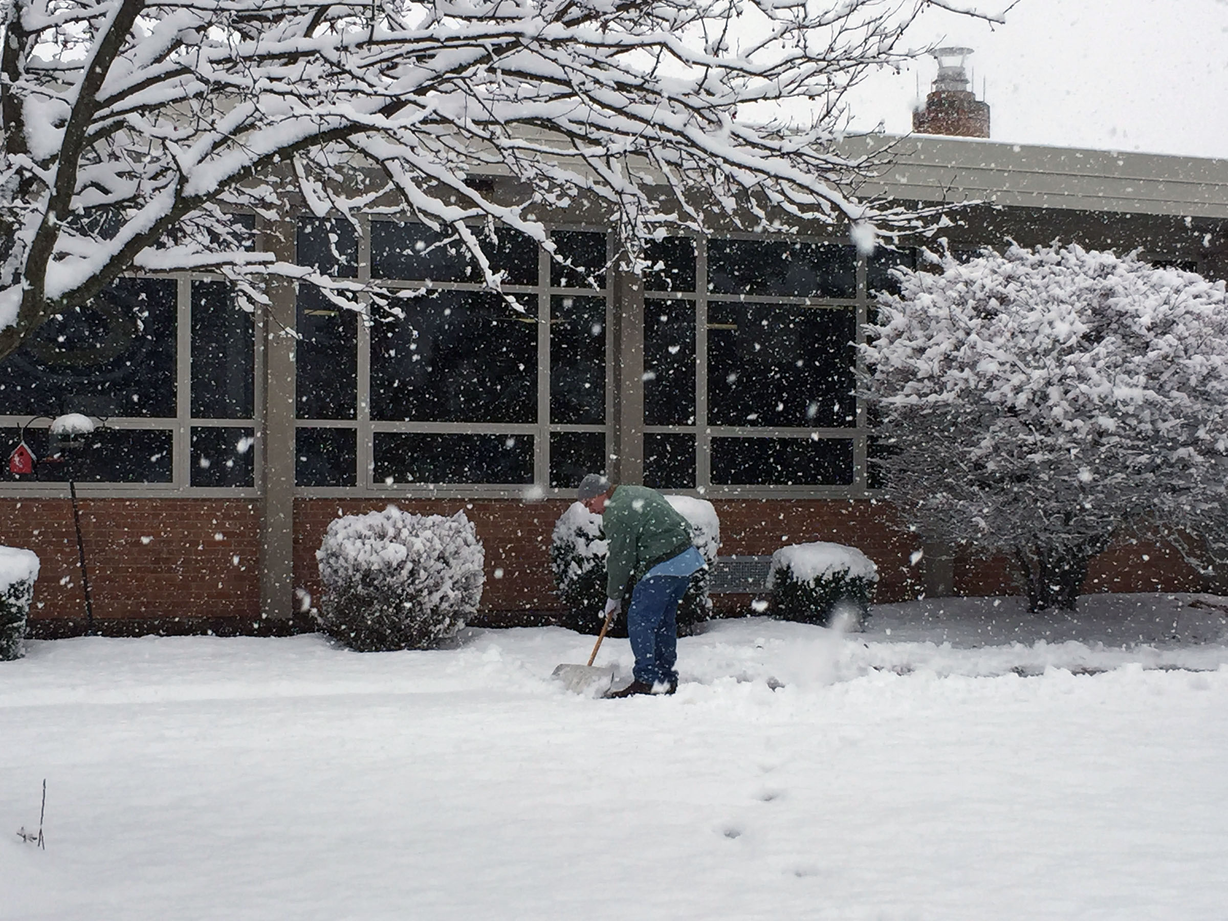 Image of custodian shoveling snow at Cline Elementary
