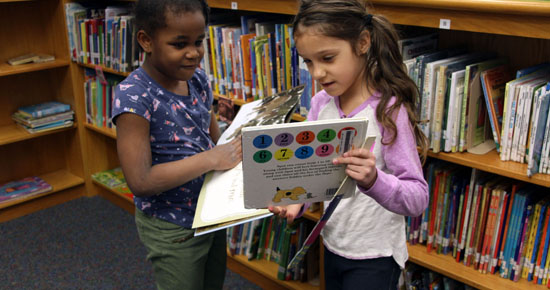 Image of two students checking out library books